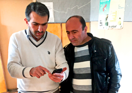 Two men looking at a phone.
